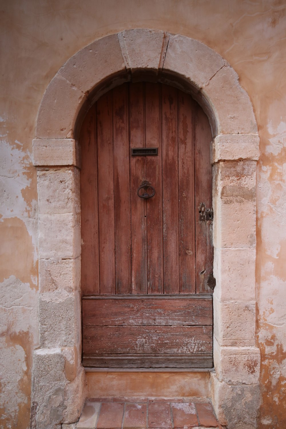 A wooden door in a pink stone wall.