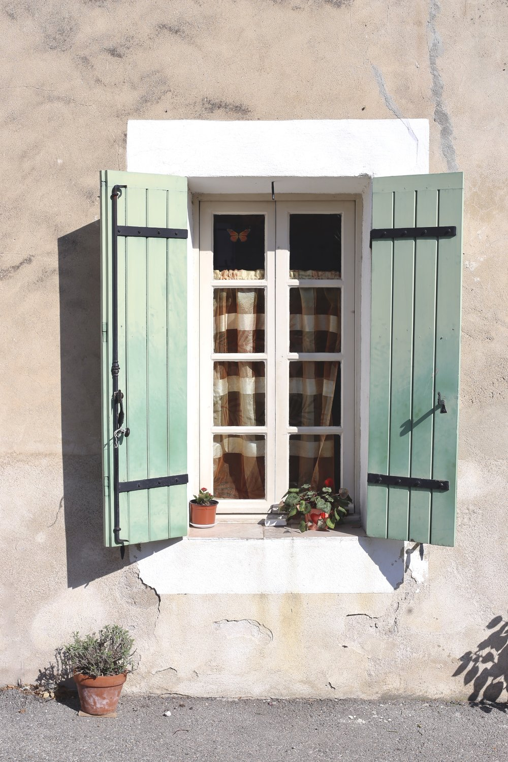 A mint shuttered window with flowerpots in Provence, in the sun.