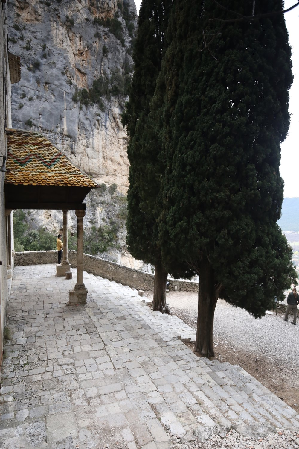 A mountain temple with standing cypress trees, in the Verdon Gorge.