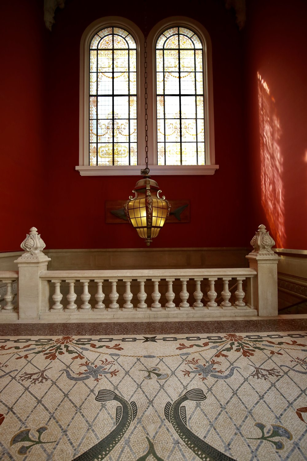 Tiled floors and drop lanterns in a grand entranceway to Monaco's museum.