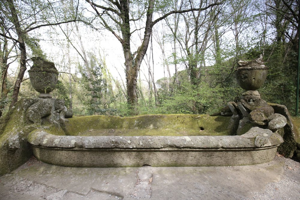 A large stone basin fountain, covered in moss.