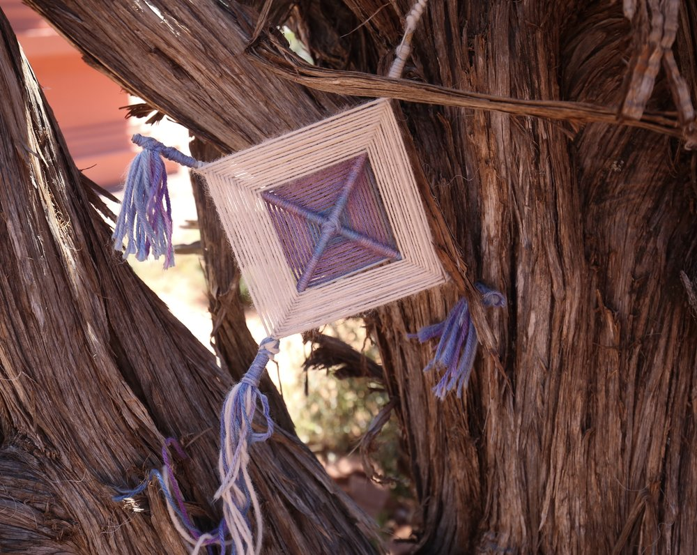 Purple woven eye, hung on a tree.