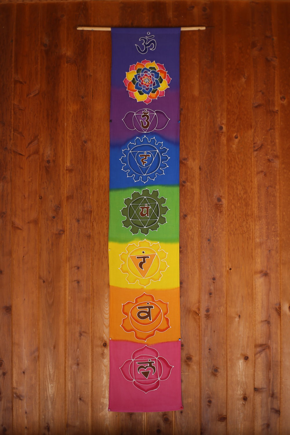 Wall hanging hand painted with the Chakras, in the pavilion of Sedona's peace gardens.