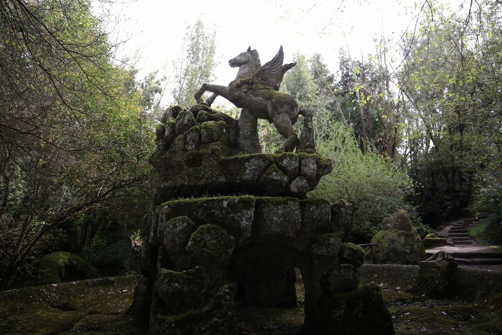 The romantic ruins of a pegasus stone fountain, in the forest of Bomarzo.