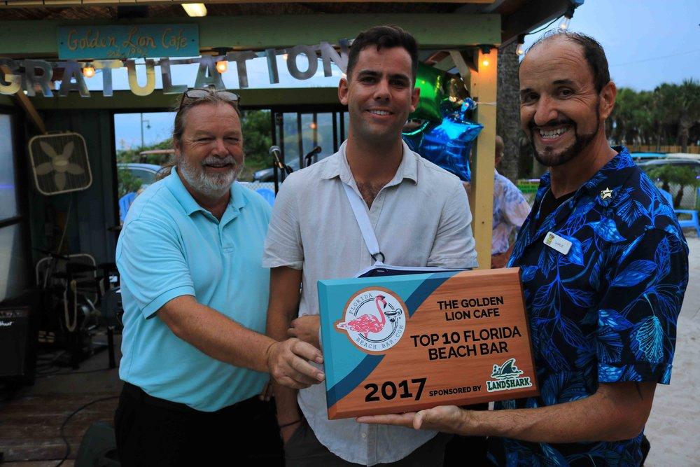 The leadership team at the Golden Lion Cafe accepts the 2017 Top 10 Florida Beach Bar award