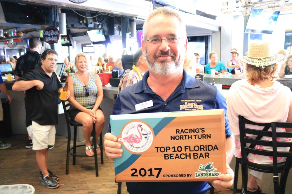 Jerry holds up the 2017 top 10 florida beach bar award at racing's north turn