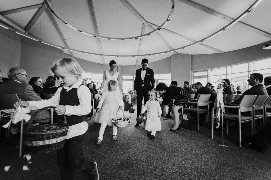 Brautpaar und Blumenkinder verlassen den Saal der Trauung