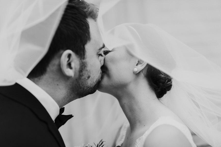 Kuss des Brautpaars unter dem Schleier