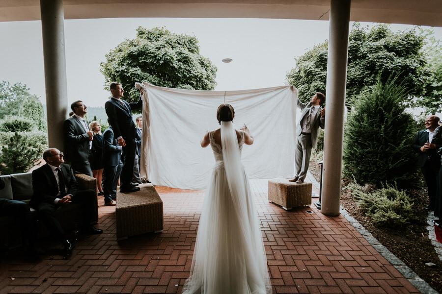 Gäste halten das Tuch, Braut versucht den drüber fliegenden Teller zu fangen