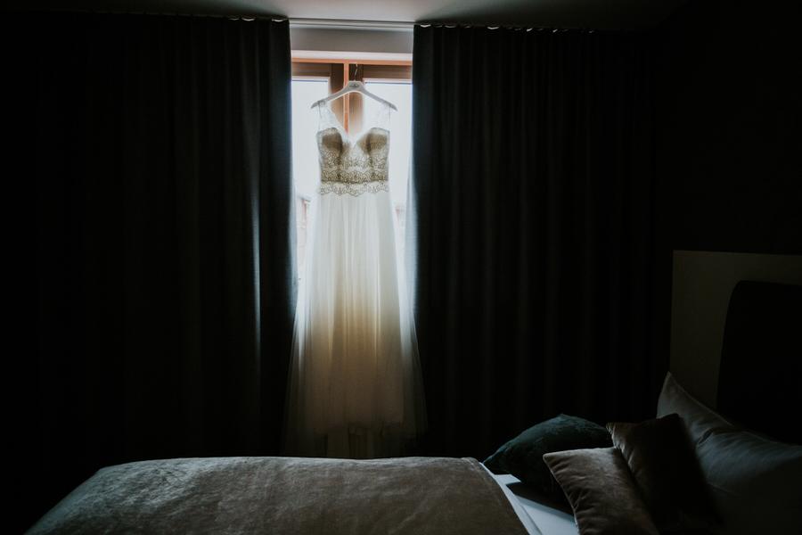 Brautkleid hängt vor Fenster im Hotelzimmer