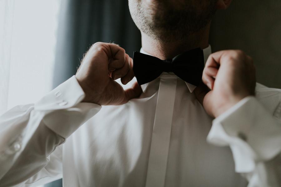 Nahaufnahme der Händen beim Anlegen der Fliege vor der Hochzeit