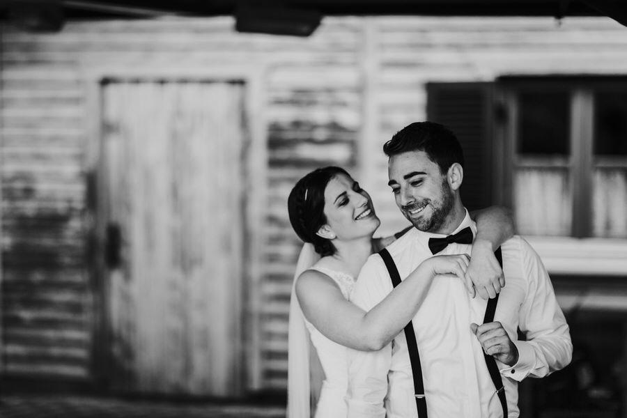 Braut umarmt Bräutigam von hinten