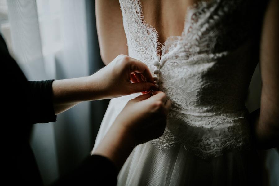 Nahaufnahme der Hände am Rücken beim Zuknöpfen des Brautkleids