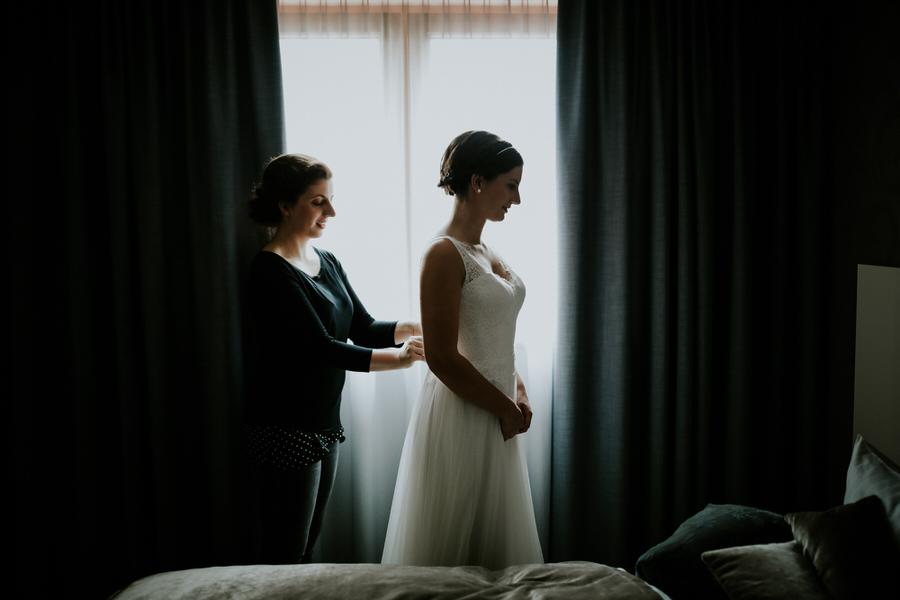 Trauzeugin knöpft das Brautkleid vor Fenster zu