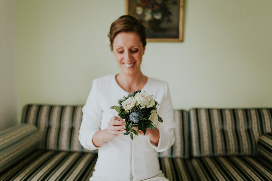 Braut bindet den Brautstrauss zusammen