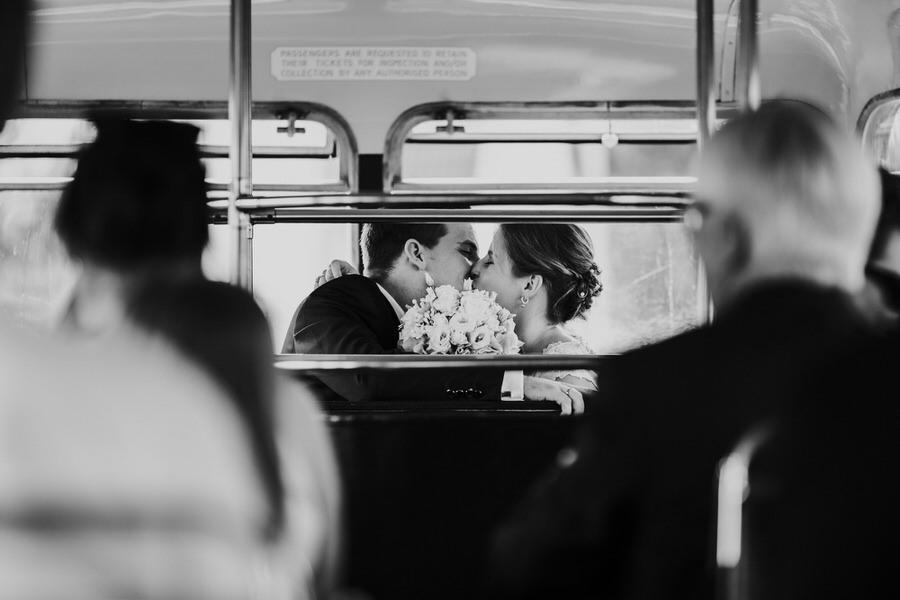 Kuss des Brautpaares im Doppeldecker waehrend der Fahrt zum Schloss Kapfenburg