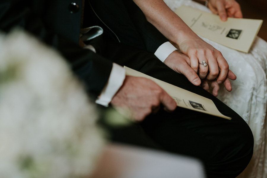 Haende des Brautpaares waehrend der Trauung mit dem Brautstrauss