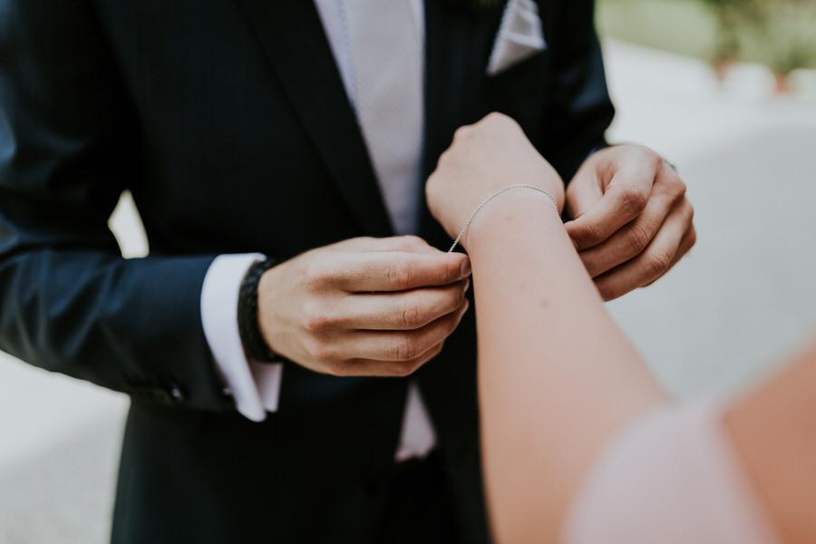 Braeutigam macht Armband an der Hand der Braut zu