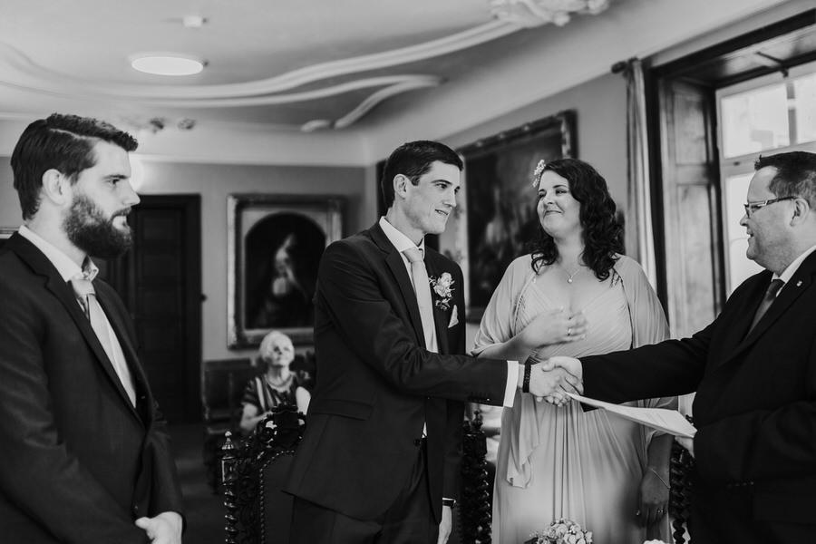 Standesbeamter gratuliert Brautpaar