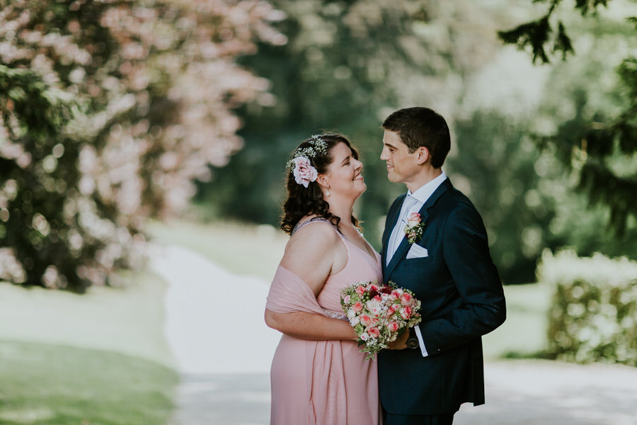 Braut im Brautkleid schaut den Braeutigam an