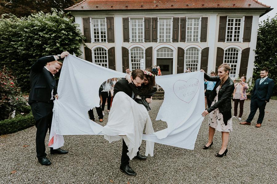 Bräutigam trägt die Braut durch das Tuch beim Spielen nach der Trauung im Ostalbkreis
