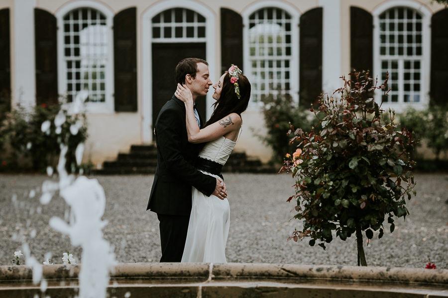 Bräutigam umarmt die Braut vor dem Brunne im Schlosspark in Abstgmünd