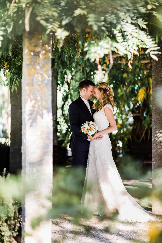 Braut in einem weißen Brautkleid steht neben dem Bräutigam beim Paarshooting auf der Insel Mainau mit Hochzeitsfotograf am Bodensee Anastasia Vyatkina
