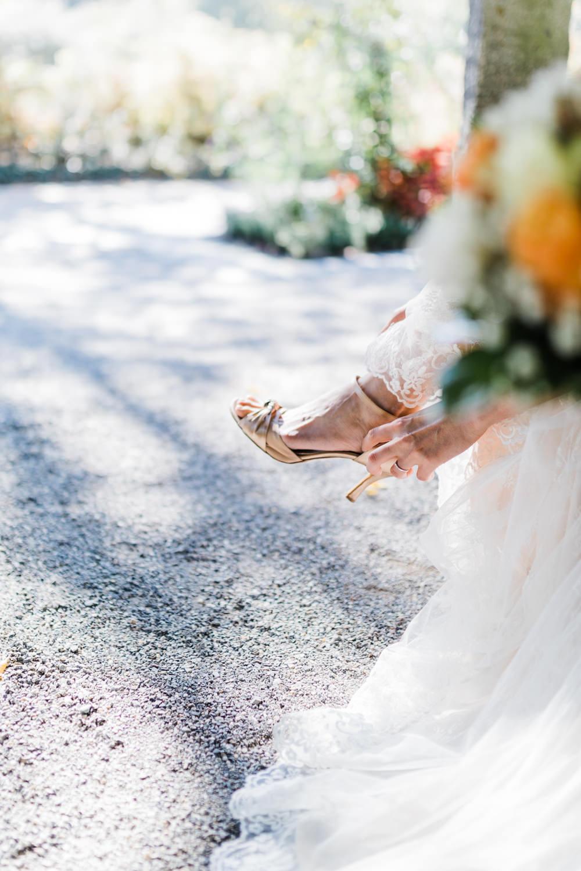 Braut zieht Brautschuhe an bei Brautpaarporträts am Bodensee mit Hochzeitsfotograf in Konstanz Anastasia Vyatkina