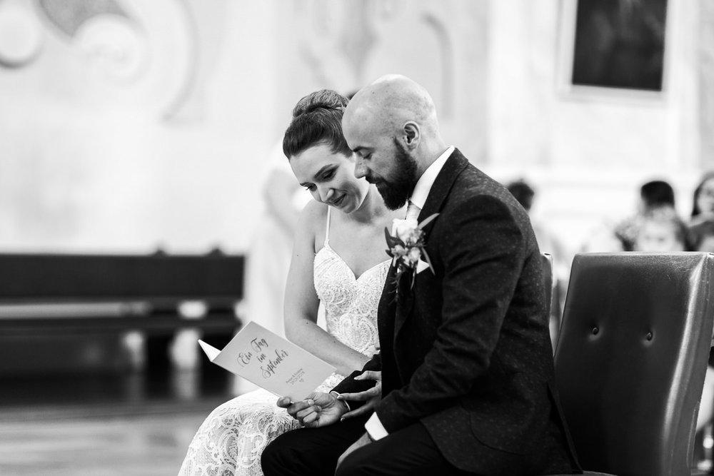 Brautpaar singt in der Kirche während der Trauung auf dem Hochzeitsbild von Hochzeitsfotografin Anastasia Vyatkina