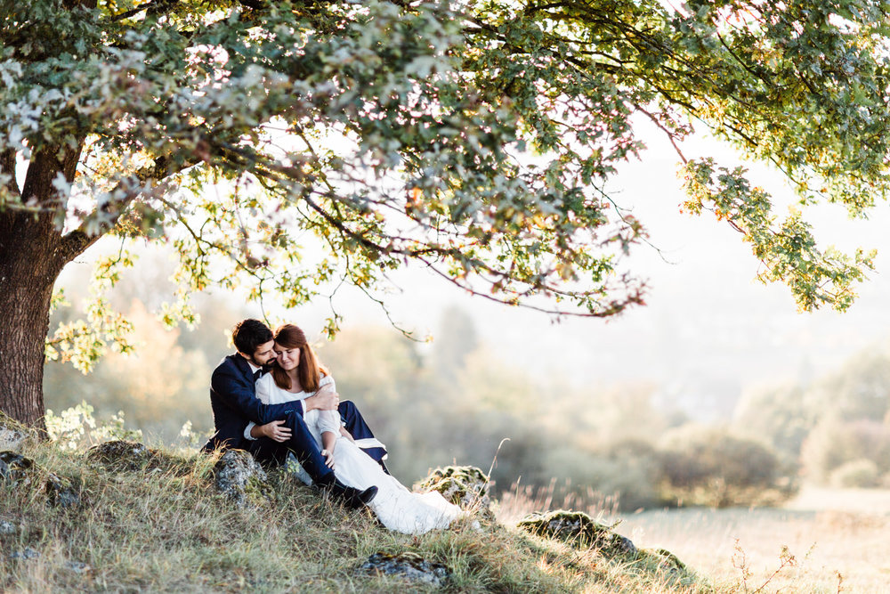 Brautpaar sitzt unter dem Baum bei Brautpaarporträts mit Anastasia Vyatkina