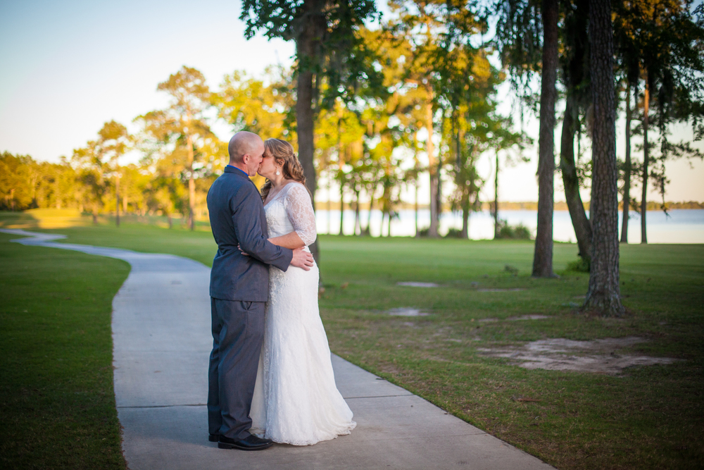 A bride and groom kiss as husband and wife after their wedding at Kingwood Country Club in Kingwood, TX.