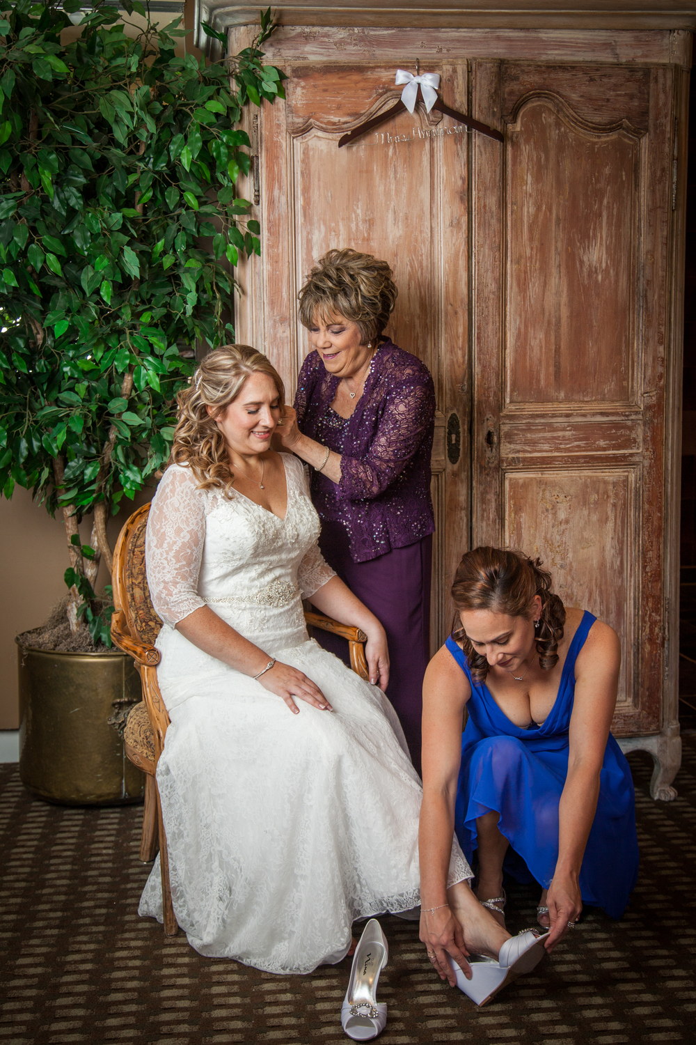 The beautiful bride in a white lace wedding gown gets ready for the ceremony with the help of her mother and sister.