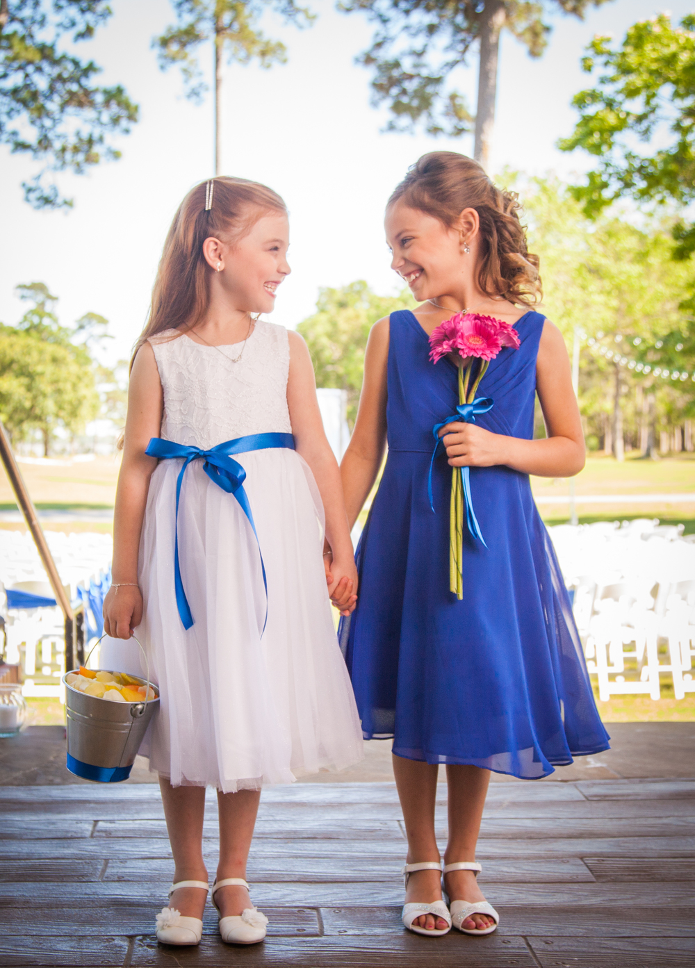 Adorable flower girls in white and blue flower girl dresses hold hands and laugh with each other before the start of the wedding ceremony.
