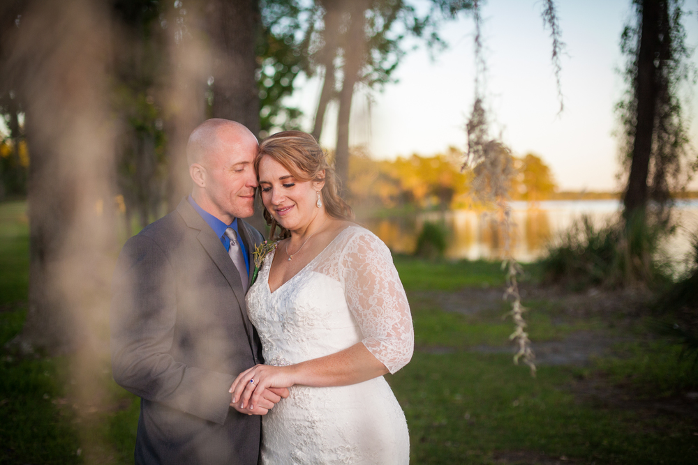 We steal the bride and groom away during the reception to capture some creative portraits just as the sun is beginning to set.  This shot was taken through a weeping willow tree for a mystical and magical feel to the image.