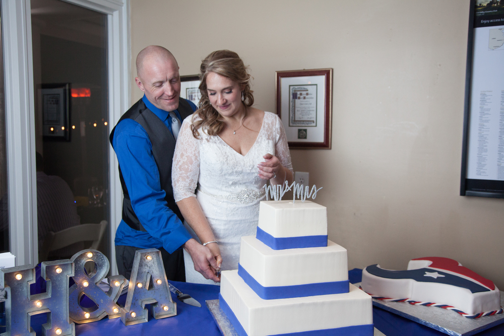 The couple cuts the white three tier wedding cake.