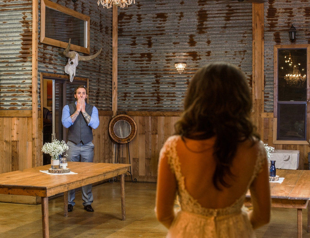 The groom sees his future wife moments before the wedding during a first look at The Barn At Four Pines Ranch in Crosby, Tx.