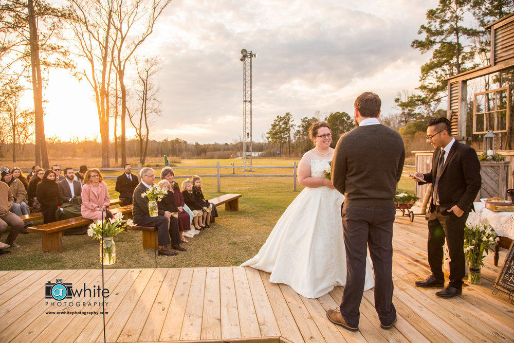 Barn wedding ceremony at sunset.