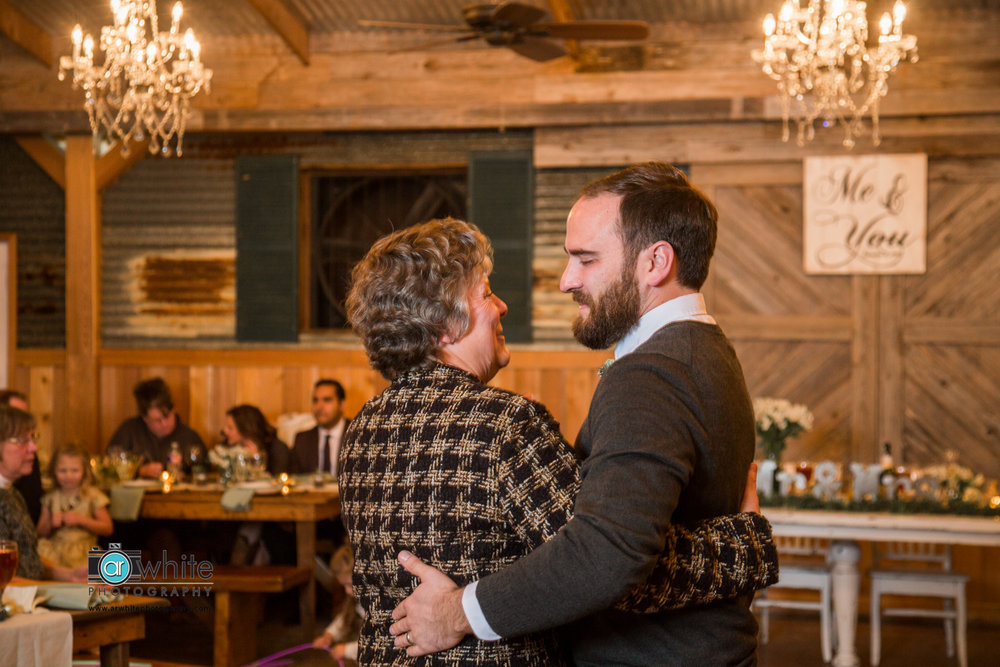 Mother and son dance at a barn wedding venue.