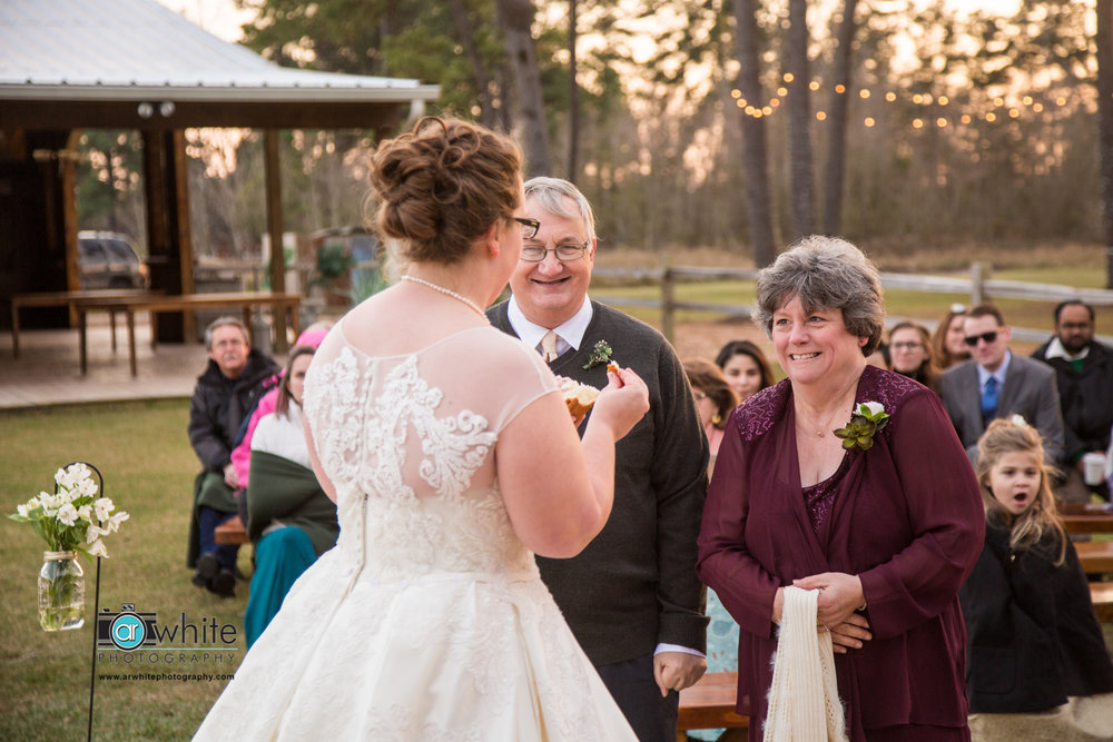 The bride gives her parents the bread offering at a farm wedding.