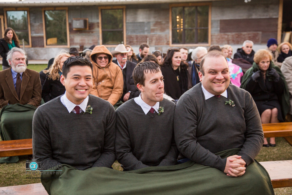 Groomsmen huddle together under a shared blanket during a cold wedding outdoors.