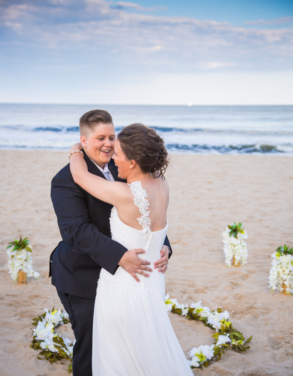 The newly married couple shares their first dance on the sand at the beach.