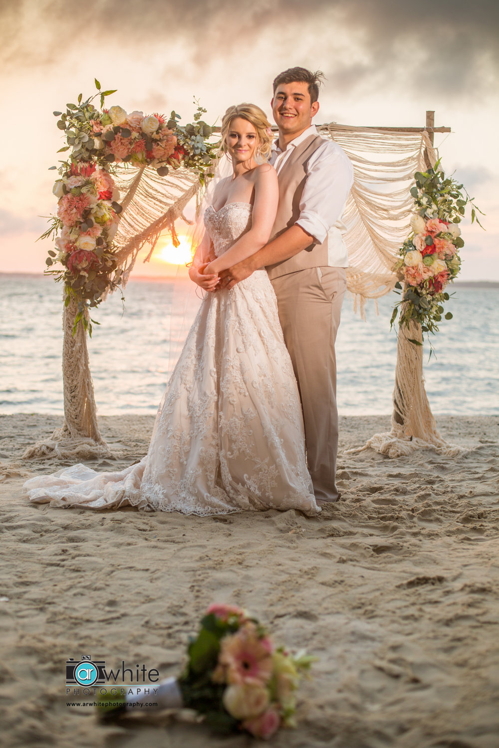 A young bride and groom pose for a photograph after their sunset wedding in Oc Maryland.