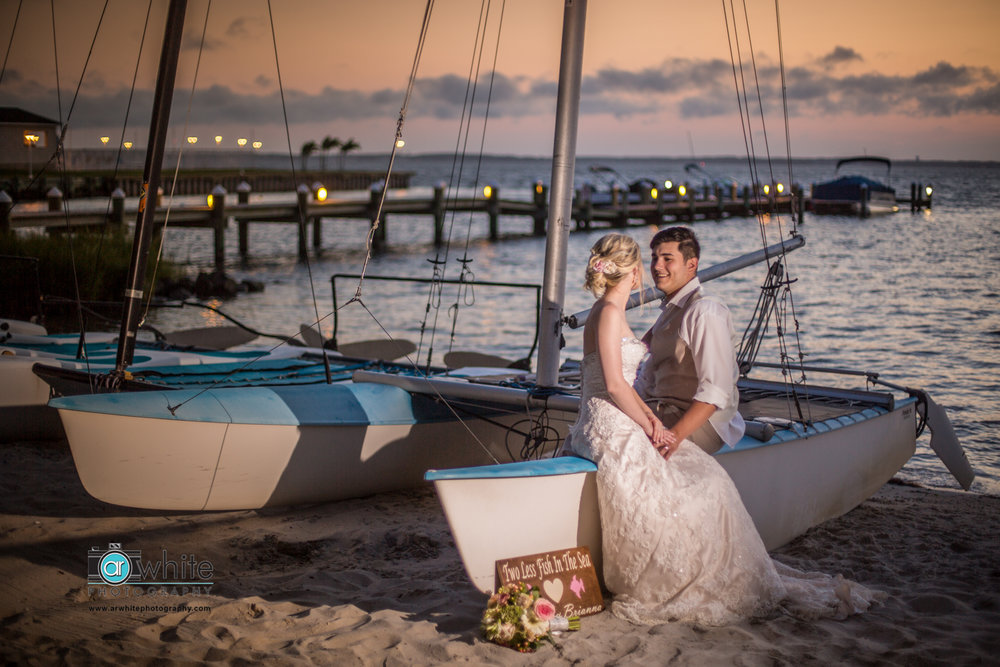 The newly married couple rest on a sailboat on the beach in Ocean City Maryland.