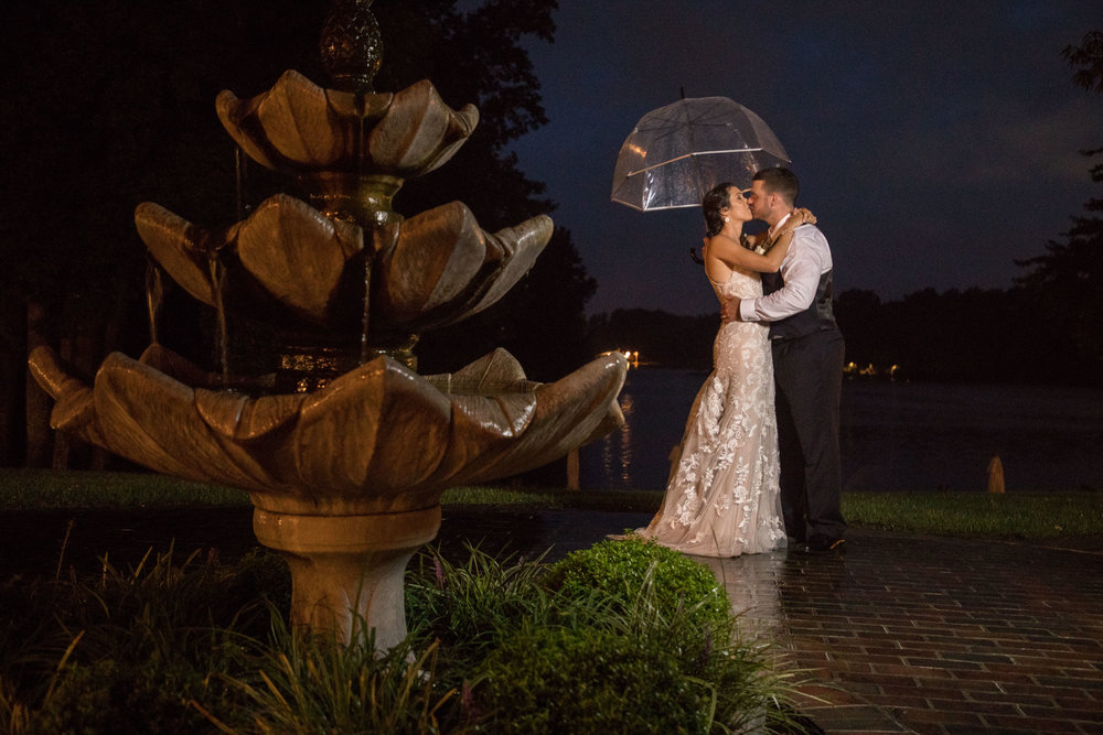 Carri and Jake share an umbrella and a kiss in the rain after the wedding ceremony.