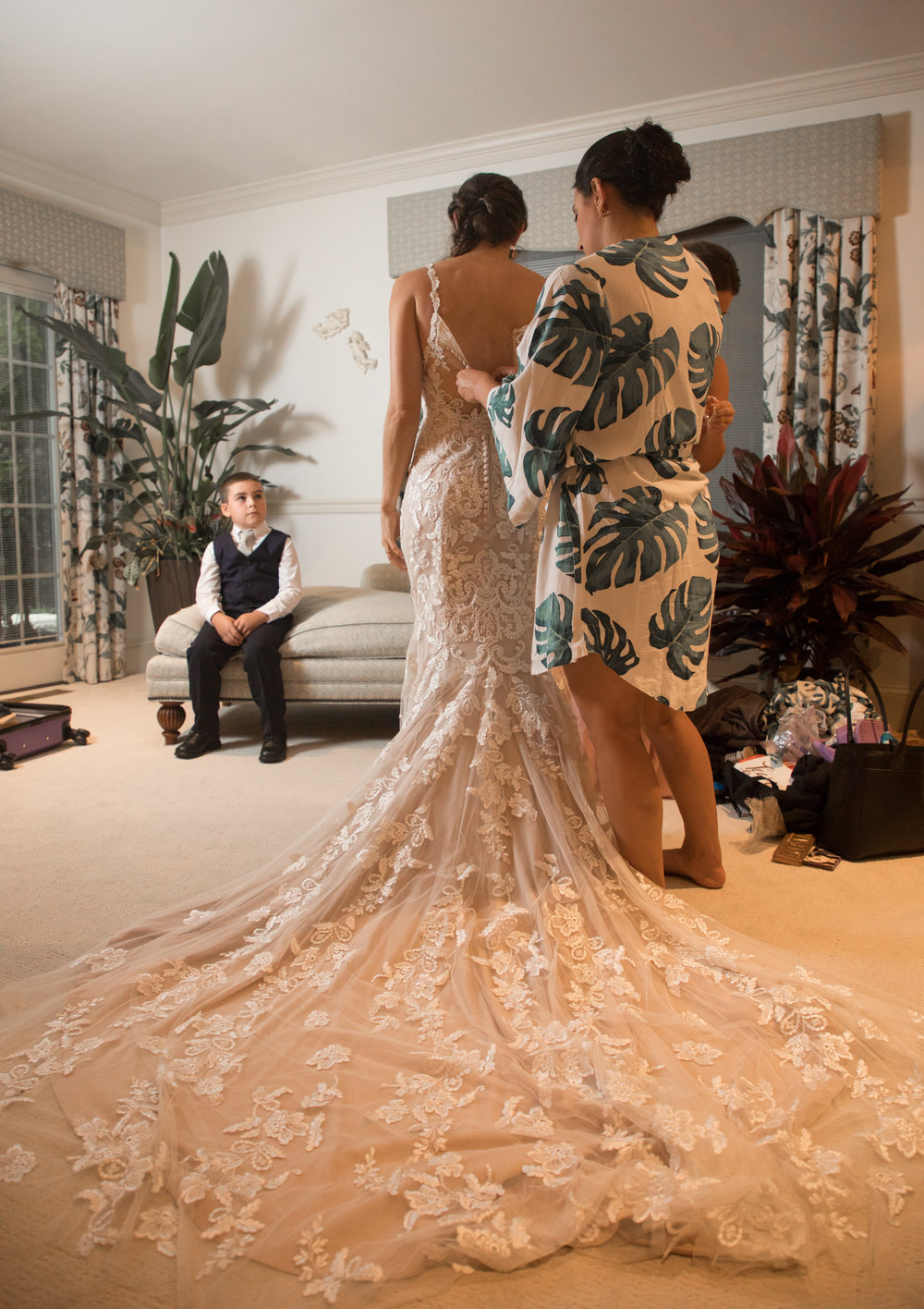 The ring bearer looks admiringly at the bride as her maid of honor buttons the back of her stunning wedding gown.