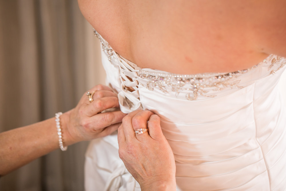 The mother of the bride helps Jenna get into her white elegant wedding gown before the start of the wedding.