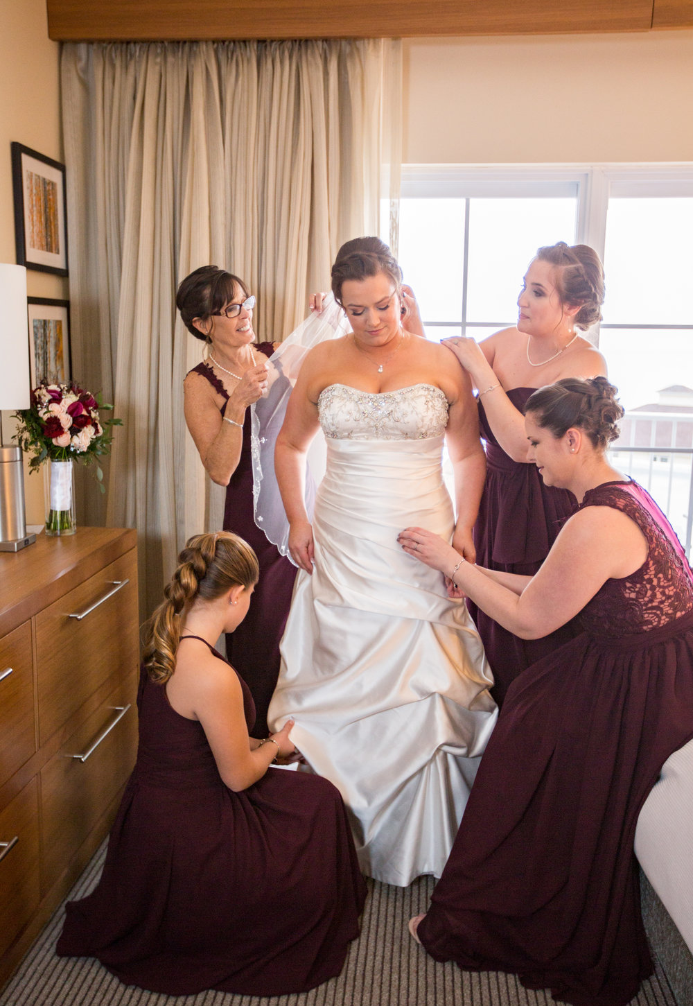 Jenna's bridesmaids help her get ready by applying some finishing touch ups.