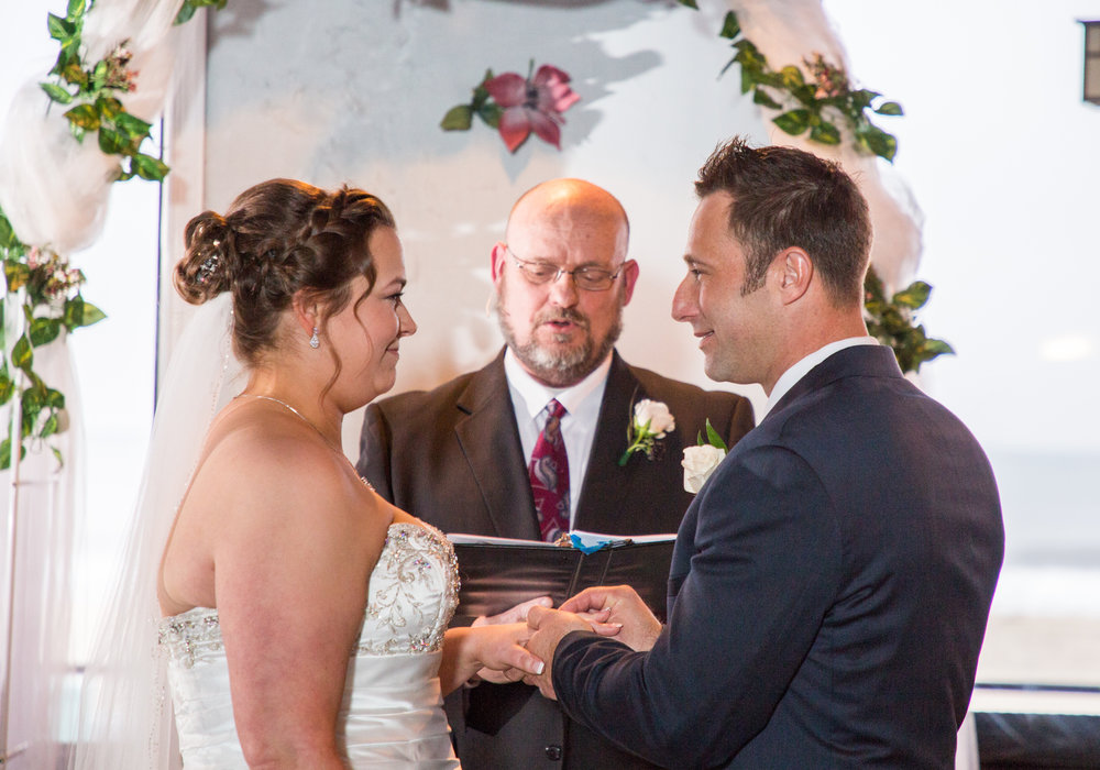 The groom put the wedding ring on the bride's finger at the wedding ceremony.