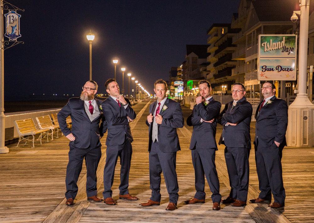 Groomsmen in their dark blue tuxedos and red ties pose on the boardwalk in Ocean City.