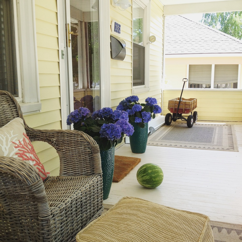 Cottage style front porch with hydrangeas and red wagon